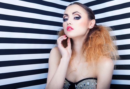 Graphic portrait of beautiful young woman with professional party make up false eyelashes on stripy background photo