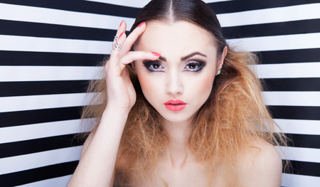 glam rock: Portrait of beautiful young woman with professional party make up false eyelashes on stripy background