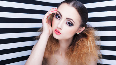 Portrait of beautiful young woman with professional party make up false eyelashes on stripy background photo