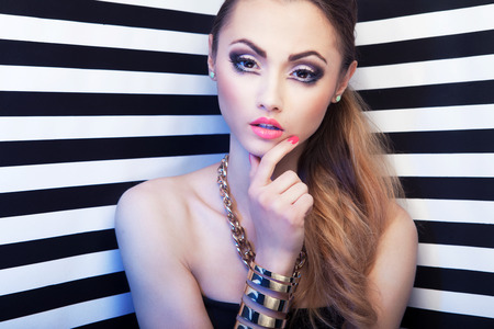 Attractive young woman with eye enlarging make up on stripy background, beauty and fashion concept photo
