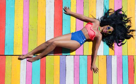 熱帯の夏の休日ファッション流行コンセプト - 木製の桟橋の背景にアフリカ系アメリカ人の女性