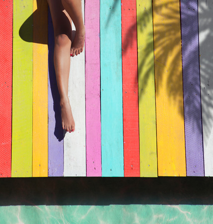 Tropical summer holiday fashion vogue concept - woman on a colorful wooden pier background