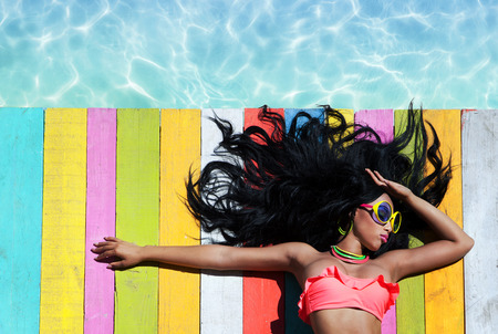 Tropical summer holiday fashion vogue concept - african american woman wearing sunglasses on a wooden pier background Stockfoto