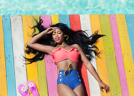 Tropical summer holiday fashion vogue concept - african american woman on a wooden pier background Stock Photo