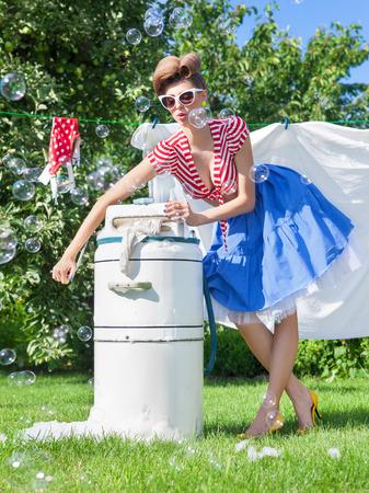 Pin up style de photo de femme faire la lessive à l'aide millésime machine à laver essoreuse Banque d'images