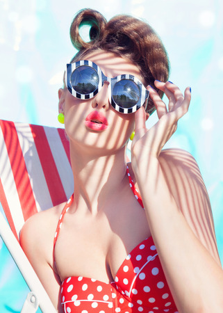 pin up: Colorful summer portrait of young attractive woman wearing bikini and sunglasses sitting by the swimming pool Stock Photo