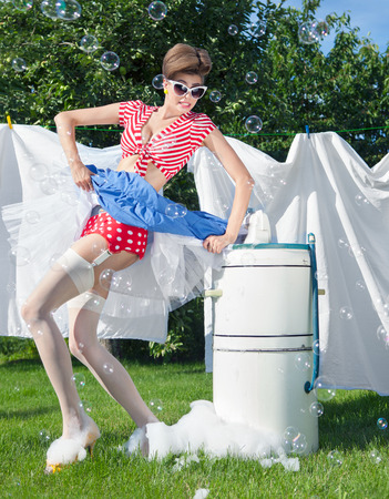 doing laundry: Skirt caught by wringer, pin up style photo of woman with vintage washing machine doing laundry outdoor Stock Photo