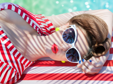 Colorful summer portrait of young attractive woman wearing sunglasses lying down by the swimming pool