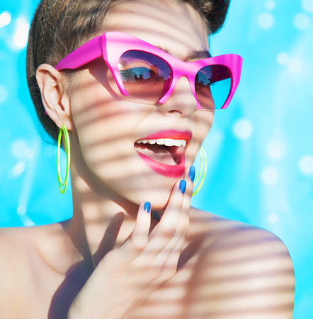 Colorful summer portrait of young attractive woman wearing sunglasses under a palm tree by the swimming pool Stock Photo