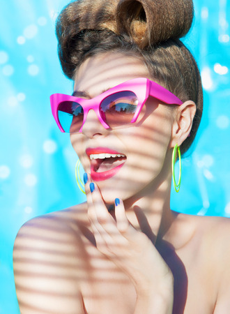 Colorful summer portrait of young attractive woman wearing sunglasses under a palm tree by the swimming pool photo