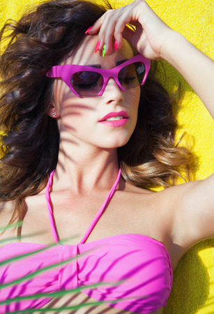 Colorful summer portrait of young attractive brunette woman wearing sunglasses under a palm tree