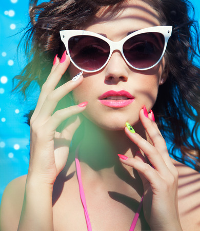 makeup model: Colorful summer portrait of young attractive brunette woman wearing sunglasses under a palm tree by the swimming pool Stock Photo