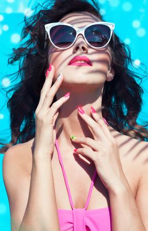 Bunter Sommer-Porträt der jungen attraktive Brünette Frau trägt eine Sonnenbrille unter einer Palme am Pool Standard-Bild - 30302523