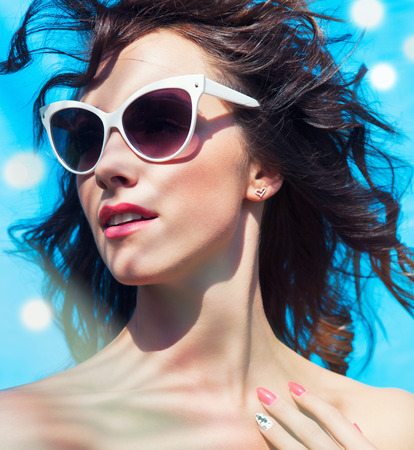 pink lips: Colorful summer portrait of young attractive brunette woman wearing sunglasses under a palm tree by the swimming pool Stock Photo
