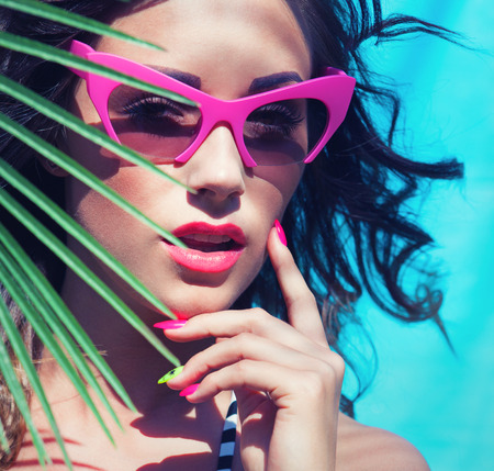 beautiful girl face: Colorful summer portrait of young attractive brunette woman wearing sunglasses under a palm tree by the swimming pool Stock Photo