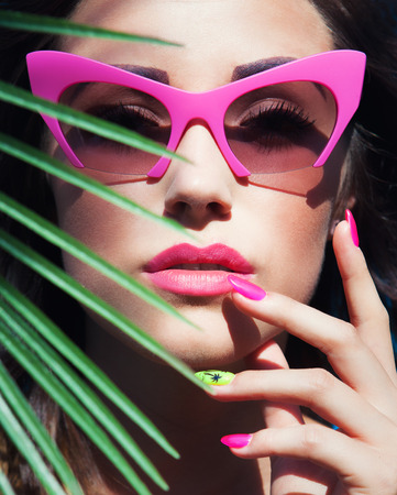 Face close up of young beautiful woman under a palm tree wearing sunglasses, summer beauty and nail art concept