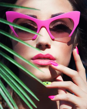Gezicht close-up van jonge mooie vrouw onder een palmboom met een zonnebril, zomer schoonheid en nail art-concept