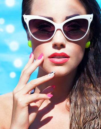 スイミング プールでサングラスを着ている若い魅力的な女性のカラフルな肖像画の夏の美しさと爪のアート コンセプト
