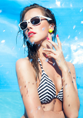 Colorful summer portrait of young attractive woman wearing sunglasses by the swimming pool Stock Photo