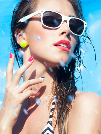 close: Colorful summer portrait of young attractive brunette woman wearing sunglasses at the swimming pool Stock Photo
