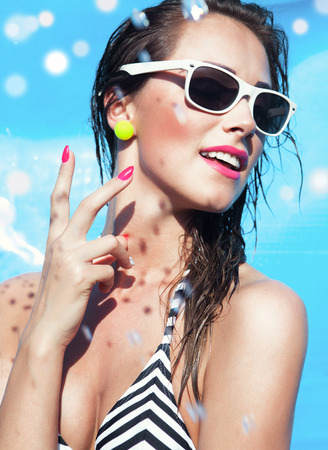 Colorful summer portrait of young attractive happy brunette woman wearing sunglasses at the swimming pool