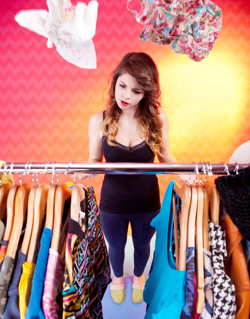 Young attractive woman searching for clothing in a closet  photo
