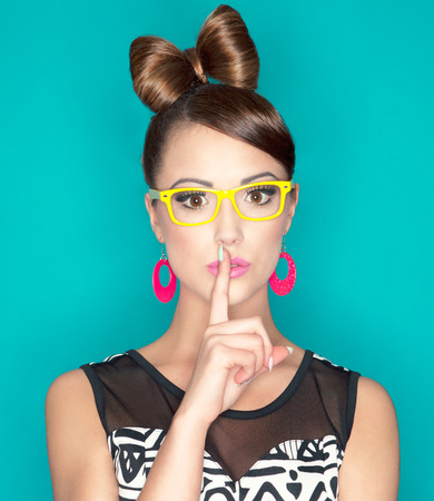 girl glasses: Young attractive fashionable woman with finger on lips, secret concept