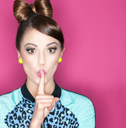 stil zijn: Jonge aantrekkelijke modieuze vrouw met een vinger op de lippen, geheime begrip Stockfoto