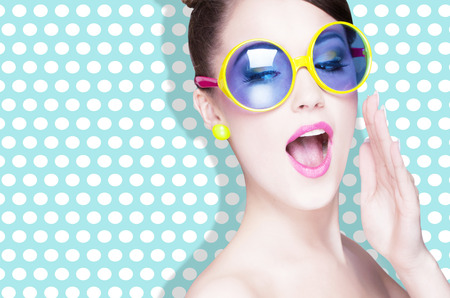 Aantrekkelijke verrast jonge vrouw draagt een zonnebril op gestippelde achtergrond, schoonheid en mode-concept Stockfoto