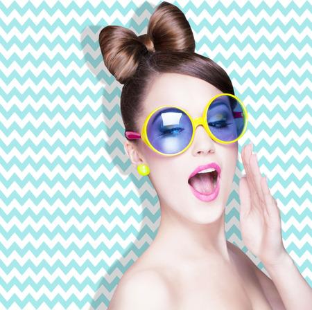 mujeres fashion: Atractiva mujer joven sorprendido con gafas de sol en zig zag de fondo, la belleza y la moda concepto