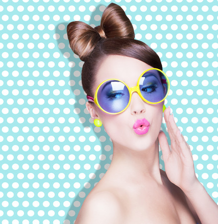 face make up: Attractive surprised young woman wearing sunglasses on dotted background, beauty and fashion concept