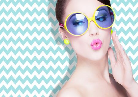 Atractiva mujer joven sorprendido con gafas de sol en zig zag de fondo, la belleza y la moda concepto Foto de archivo