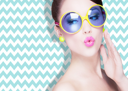face skin: Attractive surprised young woman wearing sunglasses on zig zag background, beauty and fashion concept