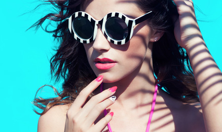 Colorful summer portrait of young attractive brunette woman wearing sunglasses under a palm tree by the swimming pool Stock Photo