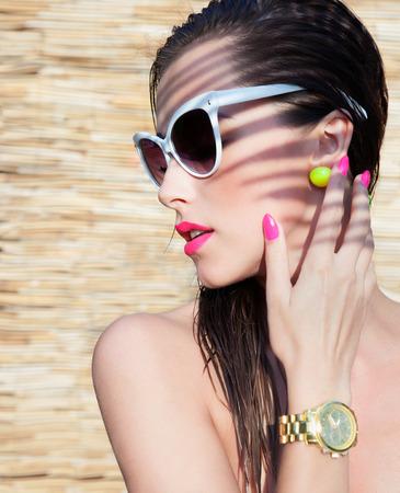 aretes: Retrato de verano de j�venes atractivas gafas de sol mujer morena con elegantes y reloj de pulsera debajo de una palmera