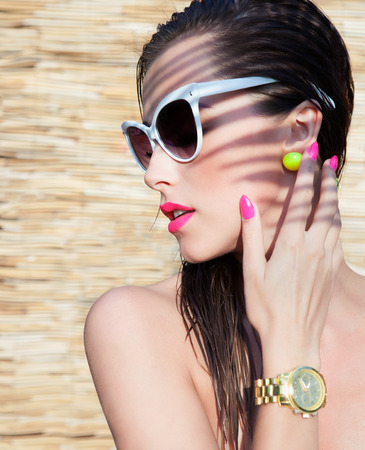 Summer portrait of young attractive elegant brunette woman wearing sunglasses and wrist watch under a palm tree Stock Photo