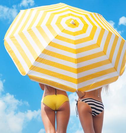 Bescherming tegen de zon en de zomer lichaam zorg concept, vrouwen het dragen van bikini onder een parasol