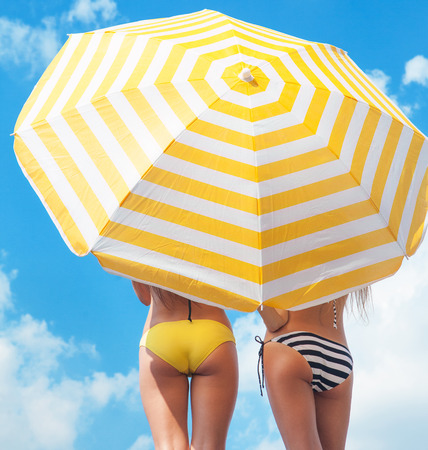 Sun protection and summer body care concept, women wearing bikini under a beach umbrella