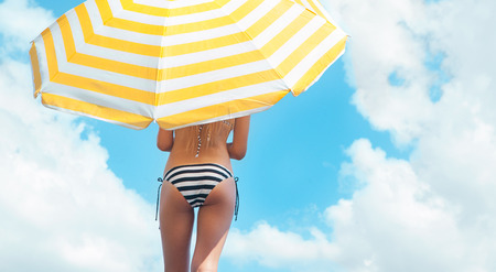 weather protection: Sun protection and summer body care concept, woman wearing bikini under a beach umbrella