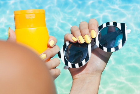 Summer fashion and beauty hand care concept, woman holding sunglasses and sunscreen lotion at the pool