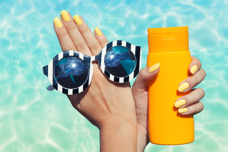 Summer fashion and beauty hand care concept, woman at the pool holding sunglasses and sunscreen lotion Stock Photo
