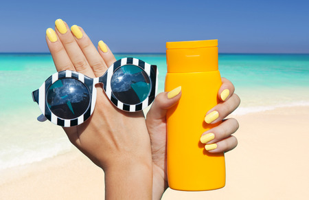 Summer fashion and beauty hand care concept, woman on the beach holding sunglasses and sunscreen lotion