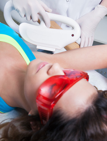 depilation: Woman getting laser treatment in medical spa center, permanent hair removal concept