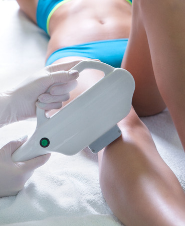 Woman getting laser treatment in medical spa center, permanent hair removal concept