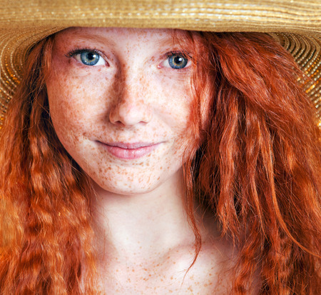 Summer portrait, beautiful freckled young woman wearing straw hat