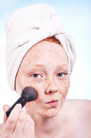 freckled: Freckled face girl applying a blush