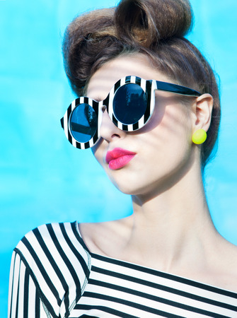 Face close up of beautiful young woman wearing stripy sunglasses Stock Photo