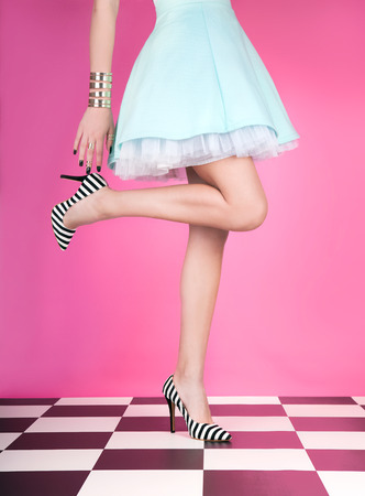 Young woman standing on one leg wearing high heels Stock Photo