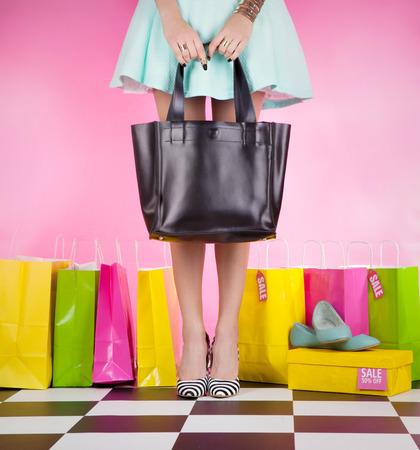 買い物袋とハイヒールを身に着けている若いトレンディな女性