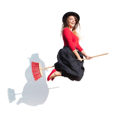 wicked witch: Happy young witch flying on a broom, halloween concept Stock Photo